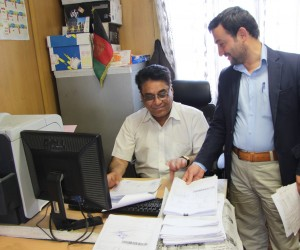 A telecommunications company employee checks with a customs official on release of his imports.