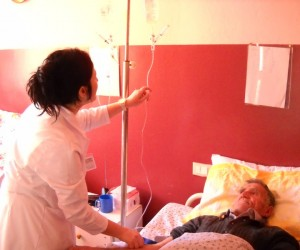 A nurse administers medication through an IV to a patient in a hospital bed