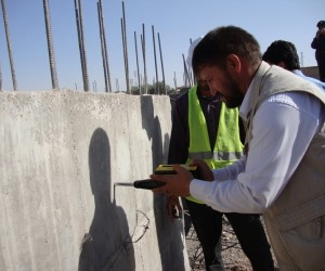 Engineer Nadir using the digital hammer to test the quality of concrete in Herat city.