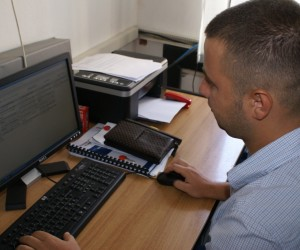 A man works in front of a computer screen