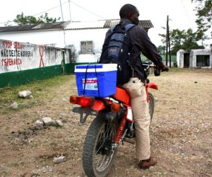 A health professional transports lab samples on a motorcycle procured with USAID support
