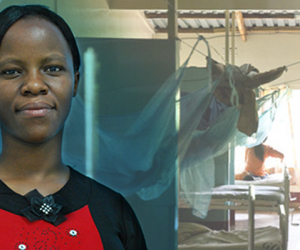 A young Kenyan woman stands facing the camera in a clinic with blue mosquito nets and hospital cots in the background.