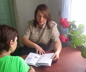 "Nurse consulting a client using a ""Patient's Diary,"" a booklet developed by USAID that tracks a patient's treatment progress."