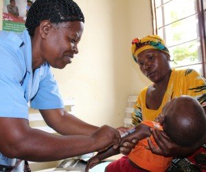 A nurse gives a child an immunization shot while his mother holds him.