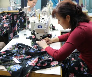 Female worker sews garment at Portavita clothing factory