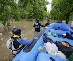 Rafters wade in waist-deep waters to rescue victims of flooding in Bosnia and Herzegovina.