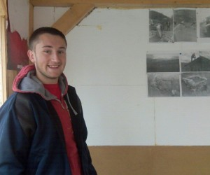 Sulejman Abazović, youth leader and peace activist in Bistrica, stands next to images of local youth working together to improve their communities.