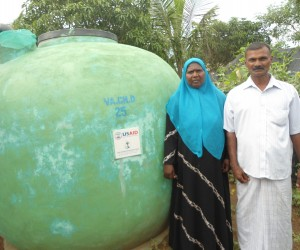 Sarifa and Khalideen in front of the rainwater harvesting tank that they have painted to give color