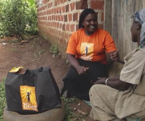 "A Solar Sister entrepreneur, left, describes how she uses her ""business in a bag"" to a customer."