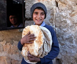 Syrian youth holding bread.