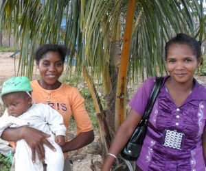 A woman holds a baby while standing with her female community health worker.
