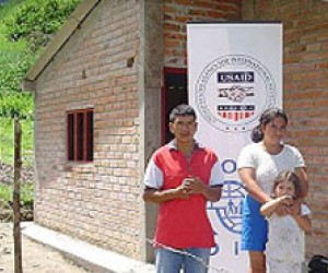 Flor and José Baca pose in front of their new home in Los Andes de Sotomayor, Nariño, which USAID helped them buil