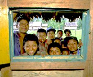 Indigenous children peer through a window at the Bosawas Biosphere Reserve.