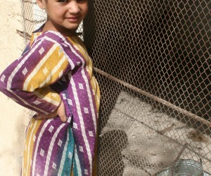 A girl in Mastung District stands by her family's new chicken coop, where the chickens stay to beat the midday heat.