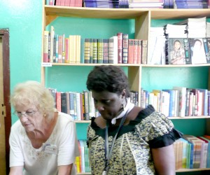 Peace Corps Response Volunteer Gloria Reichmann (left) organizes books and supplies with a local staff member at a USAID Learnin