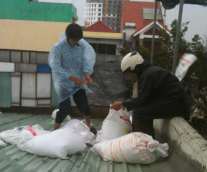 Staff prepare sandbags to reinforce the company's roof.