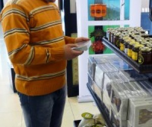 A customer compares high-quality Iraqi foodstuffs at Baghdad International Airport. The duty-free store, featuring several USAID