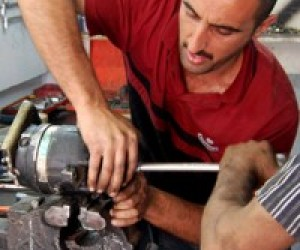Baghdad Mechanic Ahmed Hamoody repairs an auto air conditioning motor with assistance from an employee