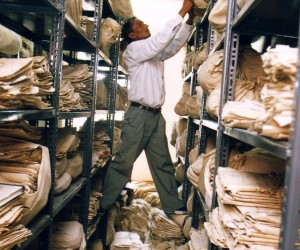 A file clerk in Nepal retrieving a sack of files from a utility shelf.