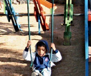 Elvio Barrios enjoys the swingset in the rebuilt playground of Ñemby's main park.