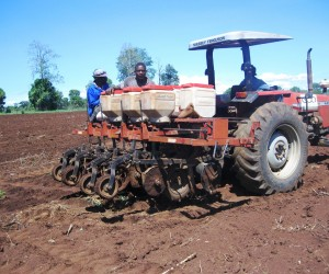 Farmers using a tractor to farm the land