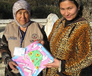 Muhabbat (left) gives her client, who has recently had a baby, a newborn kit, which includes infant clothing, a hat, a blanket,
