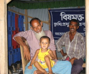 Bangladeshi farmer Nazrul Islam Khan, with his grandson on his lap, made a profit on his crops after using a melon fly trap that