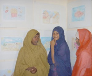 Young women display their artwork at a ceremony for students of an environmental art initiative in Egypt.