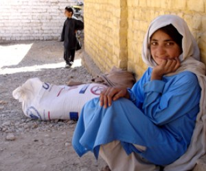 Naz Gul sits outside school in her village of Chaghai with her monthly ration of wheat for her family.