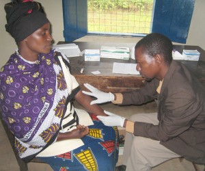 Government health worker Frank Mputa prepares to collect a blood sample from a local woman during a voluntary counseling and tes