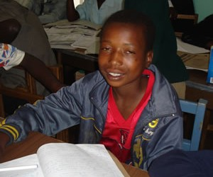 Lovemore studies at night in the streets. He hopes for a Presbyterian Children's Club scholarship for boarding school.