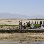 Residents improving an irrigation canal in Laghman Province. This project will help to improve the arid land seen in the backgro