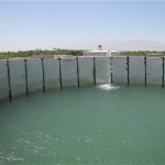 Water from Al Buroni University's new solar water pump spills into a concrete reservoir that feeds the lower farm.