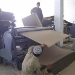 Box factory employees make cardboard sheets during the box-production process.