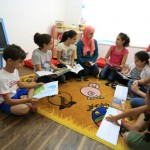 Children discuss stories they read in their weekly book club meeting with Eman Awamleh, founder of Carnaval Play & Learn.