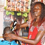 Mildred Wanjala attends to a customer at her Bungoma County barbershop