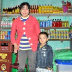 Pham Thi Gai and her son, next to the fully stocked shelves of her store.