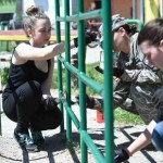 U.S. Army cadets and local students in Travnik, BiH, painting playground fence.