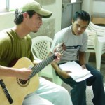 Manfer Manuel Guzmán gives a student free music lessons while volunteering at the USAID-supported Ciudad del Sol Youth Ou