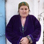 Shulabibi Ismatova stands in her yard following her recovery. The burns on her neck and chest are visible.