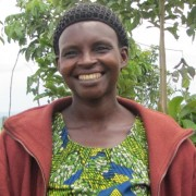 Annociate Musabwamana, center, stands with two farmers she trained under Sell More For More.