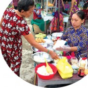A women sells sticky rice from her market stall which she created after taking project-supported business training. Photo: Pact