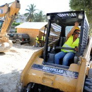 Roselette Dupervil, a heavy machinery operator, talks to a colleague from her seat inside an excavator Feb. 14 as she clears rub