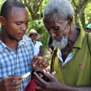 The man on the left explains how to use mobile money in Haiti's Pandiassou community as part of a USAID grant to Mercy Corps.