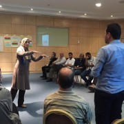 A participant in the USAID Libya Gender & Elections BRIDGE workshop engages men and women in discussion.