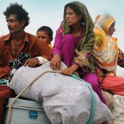 Pakistanis return home with their belongings to Bassera village in Punjab province in August 2010 as flood waters recede.