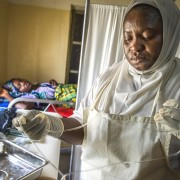 A nurse at a Nigerian health care facility gets ready to cut a mother's umbilical cord.