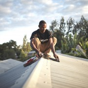 A local Off-Grid:Electric employee installs a solar home system in Tanzania.