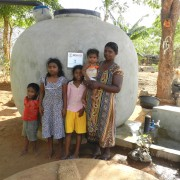 A family stands in front of their rainwater harvesting tank.