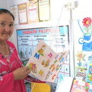 A school librarian shows off books at a library in Tajikistan established by USAID.